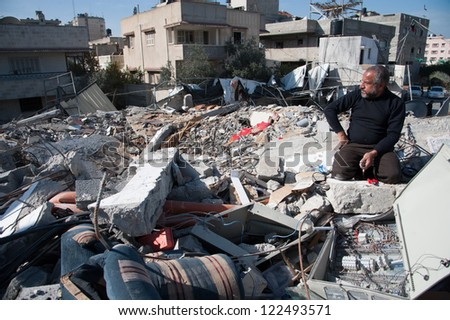 GAZA, PALESTINIAN TERRITORY - DECEMBER 3: A man combs amid the rubble of the Palestinian National Authority Council of Ministers building, December 3, 2012.
