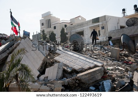 GAZA, PALESTINIAN TERRITORY - DECEMBER 3: A man combs amid the rubble of the Palestinian National Authority Council of Ministers building, December 3, 2012. - stock photo