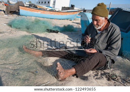 GAZA, PALESTINIAN TERRITORY - DECEMBER 2: Fisherman Naim Abu Hanoun mends his nets on the beach near Khan Younis, Gaza, December 2, 2012. - stock photo