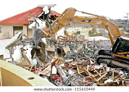 GAZA STRIP - AUGUST 31: A D-9 bulldozer is destroying an Israeli settlers home in the settlement Dugit in North Gaza Strip during Israel's unilateral disengagement plan on Aug 31 2006. - stock photo