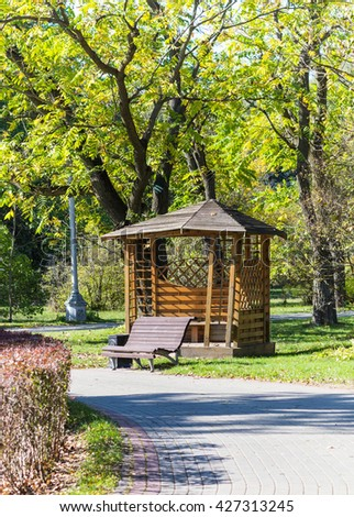 gazebo and a bench under the trees in the park - stock photo