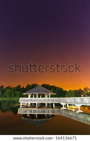 Gazebo in the middle of the lake in Vielsalm, Belgium, at night with a beautifully colored sky with lots of stars - stock photo