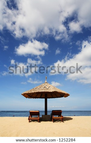 Gazebo on beautiful tropical beach. Shot against blue sky - stock photo