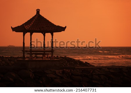 Gazebo on the ocean shore at sunset. Indonesia, Bali island - stock photo
