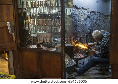 GAZIANTEP, TURKEY - MAY, 18, 2017: The knife maker sharpens the knife it produces, Copper Bazaar, Gaziantep.