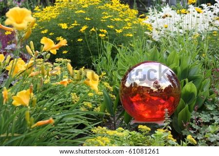 Gazing ball in beautifully landscaped yard. - stock photo