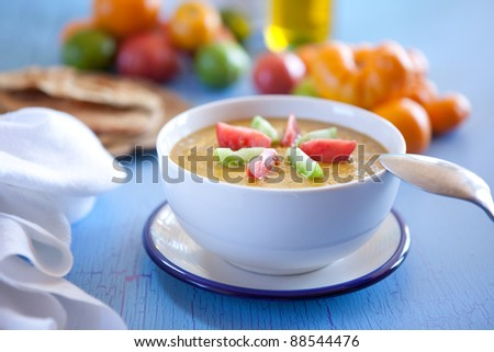 Gazpacho made with yellow tomatoes. Shallow DOF, focus on garnish tomatoes. - stock photo
