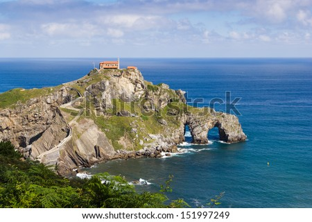 Gaztelugatxe is an islet on the coast of Biscay belonging to the municipality of Bermeo, in Basque Country (Spain). It is connected to the mainland by a man-made bridge. - stock photo