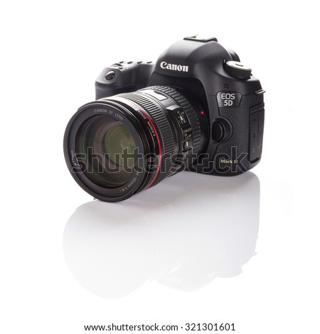 GDANSK, POLAND - FEBRUARY 18 , 2013: Canon 5D Mark III camera with 24-105mm f/4.0L IS USM lens on a white background. Canon is the world largest SLR camera manufacturer. - stock photo