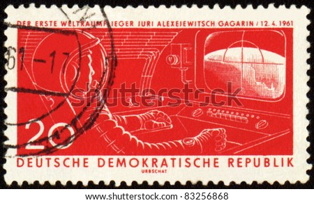 GDR - CIRCA 1961: A stamp printed in GDR (East Germany) shows first astronaut Yuri Gagarin in spacecraft cabin, circa 1961 - stock photo