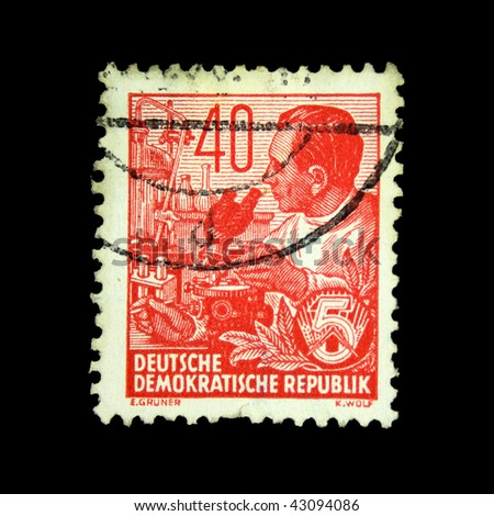 GDR - CIRCA 1958: A stamp printed in GDR (East Germany) shows scientist with a microscope, circa 1958