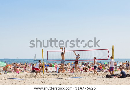 GDYNIA, POLAND - AUGUST 2, 2015: People play volleyball on Municipal beach in Gdynia city, Baltic sea, Poland - stock photo