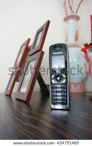 GDYNIA, POLAND - MAY 28, 2016: Panasonic home phone standing on wooden table - stock photo