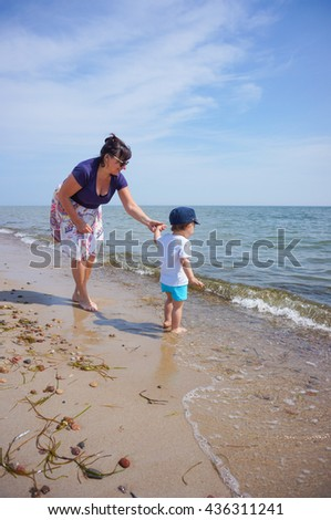GDYNIA, POLAND - MAY 28, 2016: Unidentified woman and child walking on a beach on a sunny day