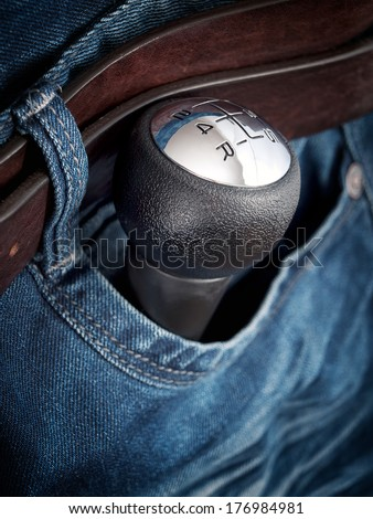 Gear shift knob in the pocket as a symbol of car enthusiasts. - stock photo