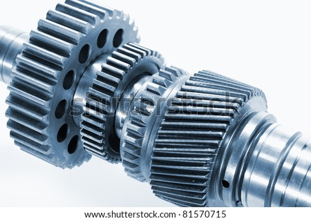 gear wheels and cogs, set against light blue backdrop - stock photo