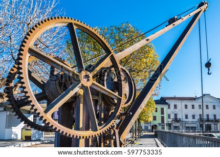 Gear wheels of an old and vintage crane. The crane is located near the small harbor on the lakeside of Luino, Lake Maggiore, Italy