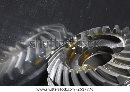 gearbox gears in lubricant-oil against shiny titanium - stock photo