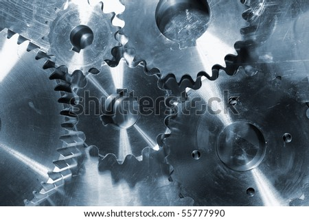 gears and cogs against steel background - stock photo