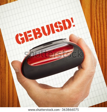 Gebuisd, failed in dutch language concept with rubber stamp in hand, paper and wooden table - stock photo