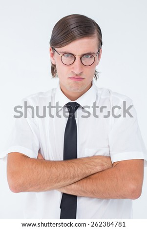 Geeky businessman looking at camera with arms crossed on white background - stock photo