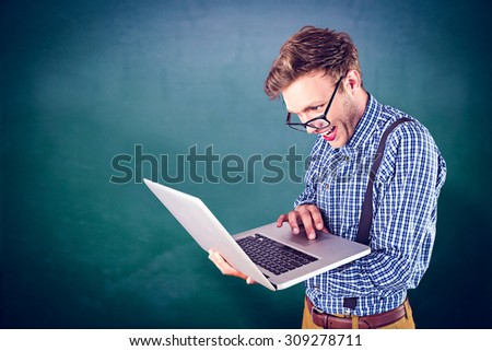 Geeky businessman using his laptop against green chalkboard - stock photo