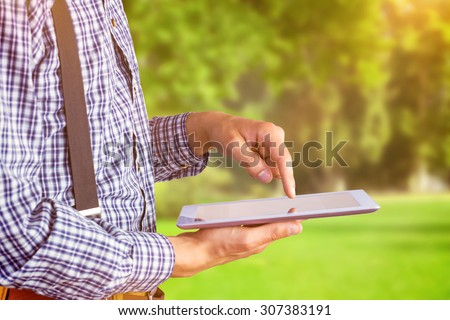 Geeky businessman using his tablet pc against trees and meadow - stock photo