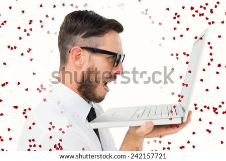 Geeky frustrated businessman looking at his laptop against red love hearts - stock photo
