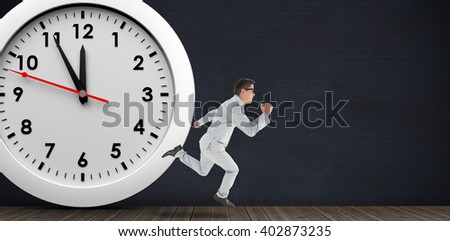 Geeky happy businessman running mid air on a black room and in front of a clock - stock photo