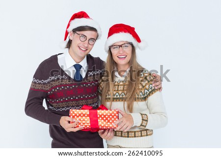 Geeky hipster couple holding present on white background
