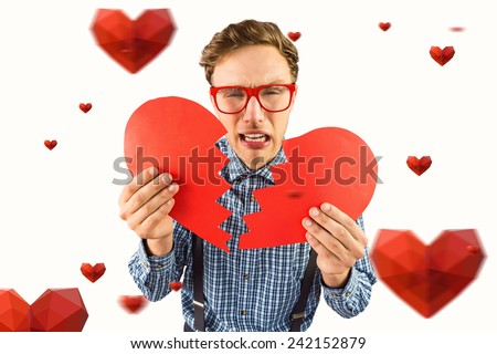 Geeky hipster holding a broken heart against hearts - stock photo