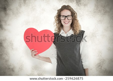 Geeky hipster holding heart card against grey background - stock photo