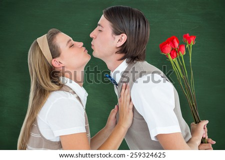 Geeky hipster holding roses and giving a kiss to his girlfriend against green chalkboard