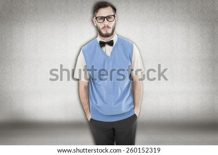 Geeky hipster looking at camera against grey room
