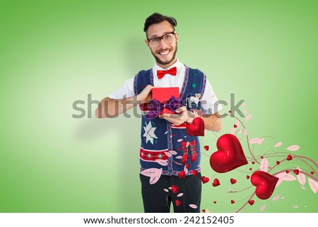 Geeky hipster offering christmas gift against green vignette - stock photo