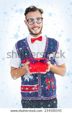 Geeky hipster offering christmas gift against snow falling - stock photo