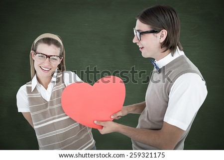 Geeky hipster offering red heart to his girlfriend against green chalkboard - stock photo