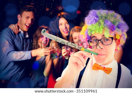 Geeky hipster wearing a rainbow wig blowing party horn against happy friends drinking shots smiling at camera - stock photo