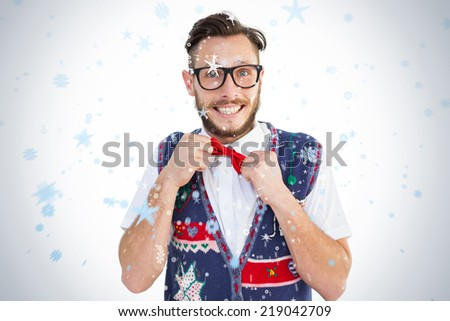 Geeky hipster wearing christmas vest against snow falling - stock photo