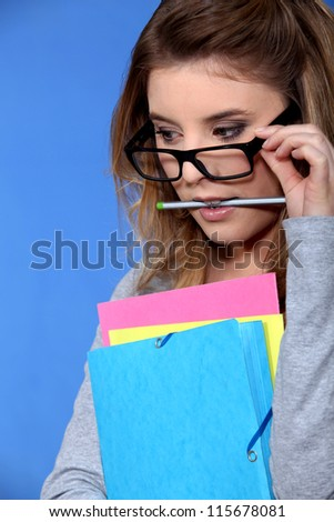 Geeky student holding folders - stock photo