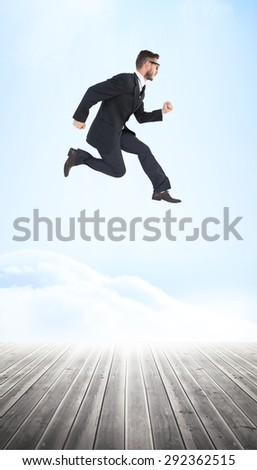 Geeky young businessman running mid air against wooden planks leading to bright sky