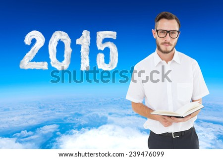 Geeky young man reading from black book against blue sky over white clouds - stock photo