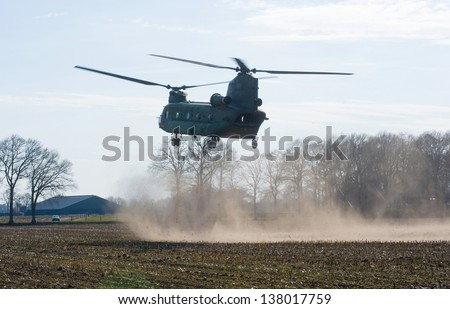 GEESTEREN, NETHERLANDS - MARCH 25: A Dutch Chinook helicopter is about to land on a field near a farm to pick up military soldiers during a training, March 25, 2013. - stock photo