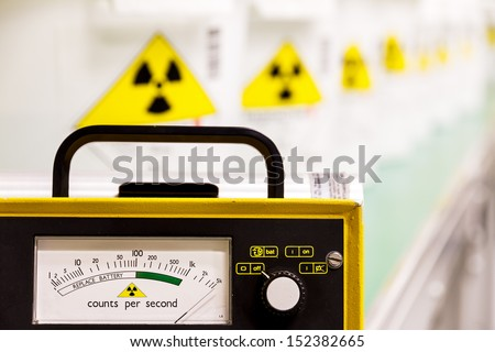 Geiger counter with radioactive materials in the background - stock photo