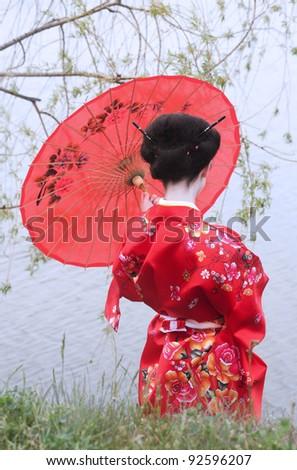 Geisha with red umbrella - stock photo