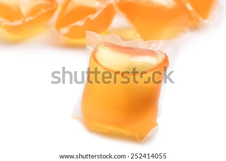 Gel capsules with laundry detergent isolated on white - stock photo