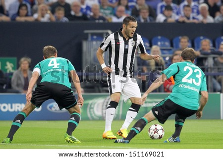 GELSENKIRCHEN, GERMANY -AUG 21: Howedes (L) of Schalke in action with Lucas (M) of Paok and Fuchs (R) of Schalke during the play-off match Schalke vs PAOK on Aug 21,2013 in Gelsenkirchen, Germany.