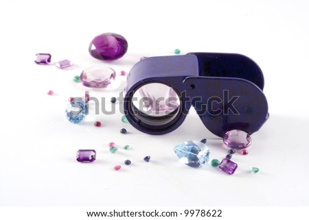 Gemstones scattered around a jewelers loupe. - stock photo