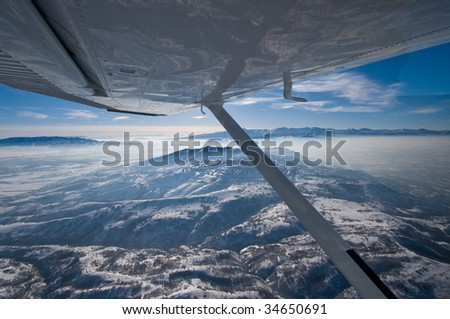 General aviation aircraft flying over Salt Lake City inversion - stock photo