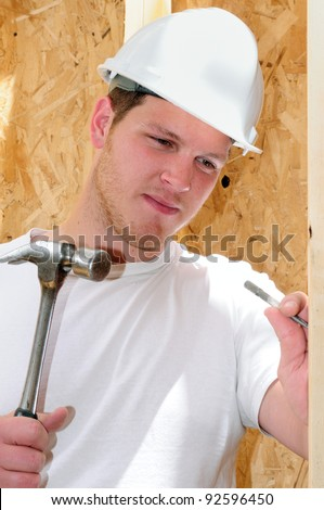 General Contractor Builder Using A Hammer While Building A New Home - stock photo